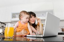 Freelancing benefits - a stay- at-home mom works on a laptop in kitchen while taking care of a young child